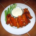 A plate of Buffalo Wings with Celery and Blue Cheese Dressing